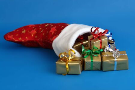 Red christmas sock full of presents wrapped into golden paper over blue background photo
