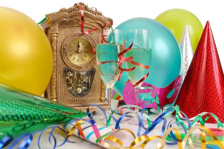 Table clock showing almost New Years time, streamers, balloons, party hats and two glasses of champagne photo