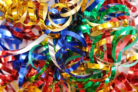 clutter: Closeup of twisted and tangled party streamers in blue, silver, red, green and golden color