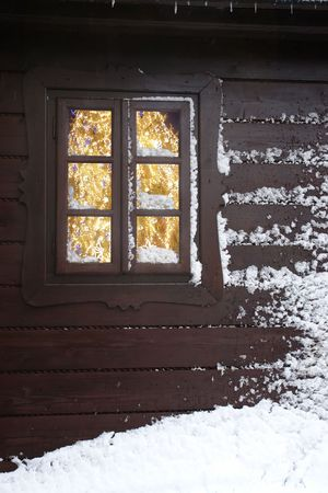 cabin: Christmas tree with lights seen through a wooden cabin window Stock Photo