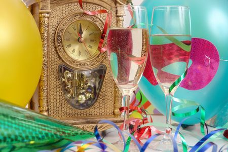 Table clock showing almost midnight, streamers, balloons, and two glasses of champagne photo