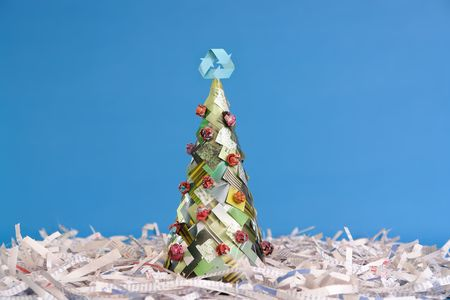 cuttings: Ecological christmas tree made of newspaper cuttings with recycle three-arrow symbol on top over blue background Stock Photo