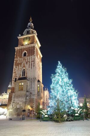 christmas tree illuminated at night standing next to historical Town Hall tower on the Main Market Square in Krakow
