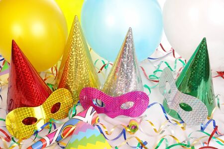 Four cone party hats, streamers, balloons and carnival masks