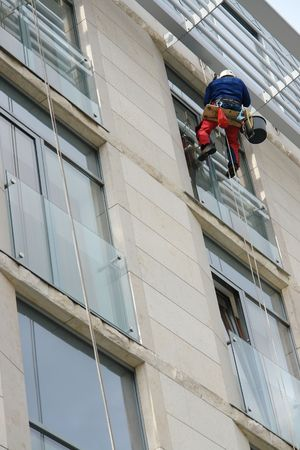 Window washer washing office building windows hanging outside the building on ropes photo