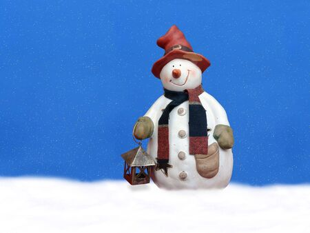 Snowman with red hat holding small lantern over snowing sky Stock Photo - 2302659