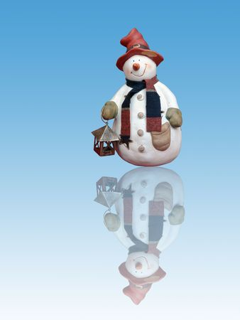 Snowman with red hat holding small lantern, reflecting in blue ice floe Stock Photo - 2302657