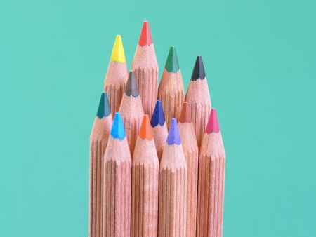 breen: Bunch of colorful wooden crayons over green background Stock Photo