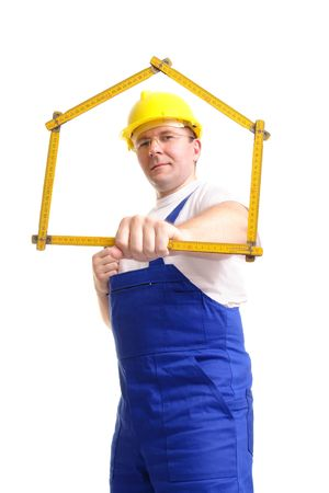 Builder wearing blue jumpsuit and yellow helmet holding wooden ruler folded in house shape - over white background Stock Photo - 2327917