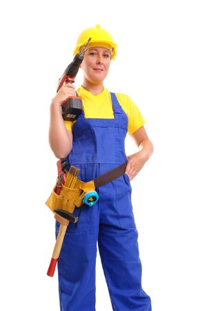 maching: Female construction worker wearing toolbelt, yellow helmet and blue overall posing with drilling maching over white background