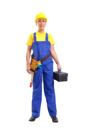 servicewoman: Service woman in blue overall  and yellow helmet wearing leather toolbelt with tools, holding black toolbox over white