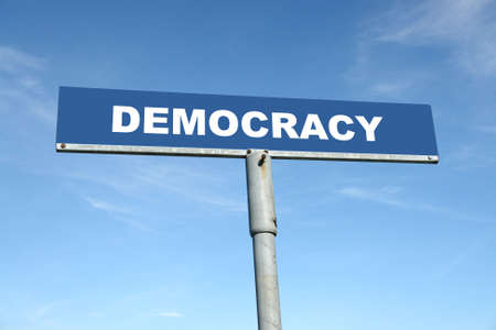 political system: Metal signpost spelling Democracy over blue sky