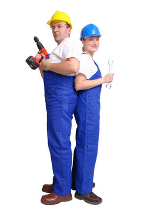 servicewoman: Serviceman and servicewoman wearing helmets and blue overall standing back to back - man holding driller, woman holding spanner - isolated on white background