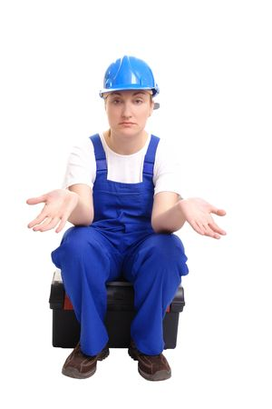 Female builder wearing blue helmet and jumpsuit sitting on toolbox spreading hands hopelessly over white photo