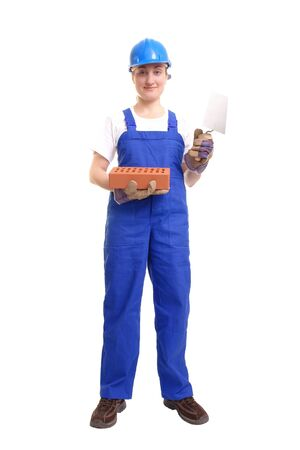 Female construction worker wearing blue jumpsuit and helmet holding stainless steel trowel and brick over white background photo