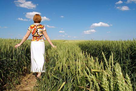 skimming: Mujer en blusa de flores en blanco y falda paseando aliado a trav�s de los cultivos de trigo descremado delicadamente las orejas de ma�z con su palma de la mano