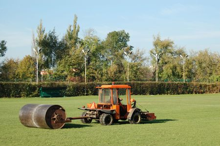 leveling: Tractor leveling soccer field grass using heavy metal lawn roller Stock Photo