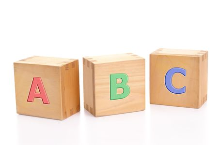 Three wooden letter blocks with first three letters of alphabet isolated on white background