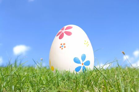 Painted easter egg in grass over blue sky