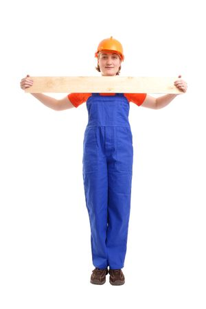 Female builder wearing blue jumpsuit and helmet holding wooden plank in front of her - over white background photo