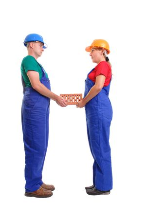 Male and female builders wearing helmet and blue overall holding together brick over white background photo