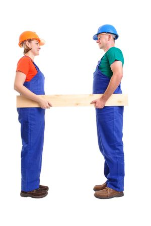 Female and male builders wearing jumpsuits and helmets holding wooden plank - over white background Stock Photo - 2521803