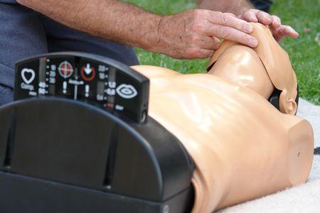 firstaid: Hombre mayor resustitation practicando la t�cnica del maniqu� de primeros auxilios durante las clases de formaci�n Foto de archivo