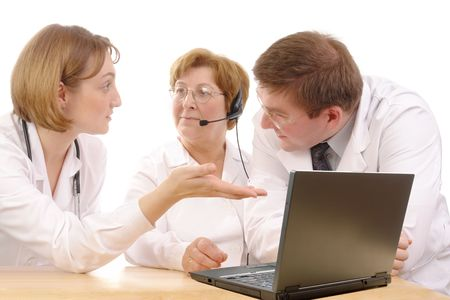 Two young interns consulting medical problem with senior doctor wearing headset sitting behind desk with laptop over white photo