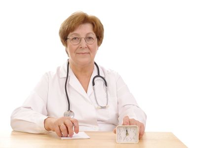 Senior family doctor with stethoscope sitting behind a desk with fingers put on alarm clock - concept to remind its high time to take care of your health photo