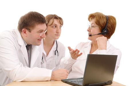 medical personnel: Two young interns consulting medical problem with senior doctor wearing headset sitting behind desk with laptop over white