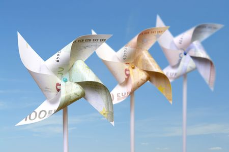20 euro: Three toy windmills cut from 100, 50 and 20 euro banknotes over blue sky Stock Photo