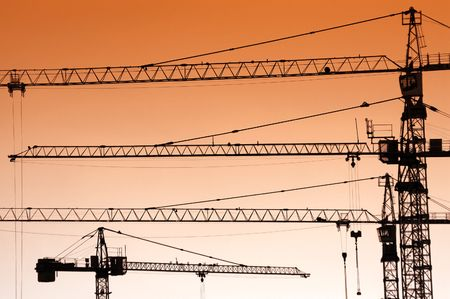 an erection: Group of jib crane silhouettes over orange sunset sky