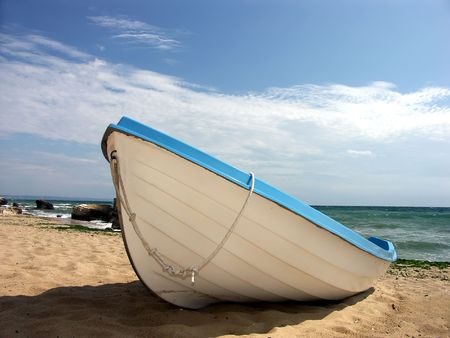 Fishermans boat made fast nearshore on sandy beach photo