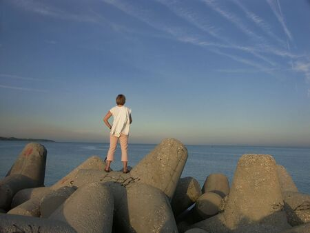 piling: Girl with white shirt standing on concrete jetty piling facing the sea after sunset