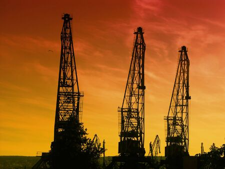 Silhouettes of giant cranes at the port of transhipment against a bloody sunset sky photo