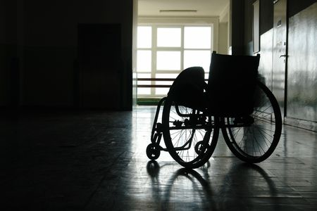 Silhouette of empty wheelchair parked in hospital hallway