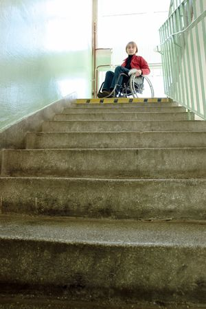 woman stairs: Handicapped woman on wheelchair looking down the stairs in building staircase