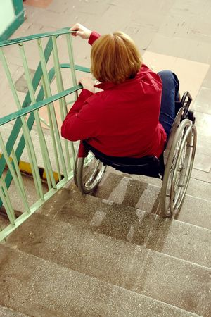Handicapped woman on wheelchair going downstairs in building staircase