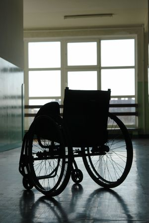 health facilities: Silhouette of empty wheelchair parked in hospital hallway