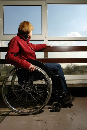 Handicapped woman sitting on wheelchair looking sorrowfully through the hospital window