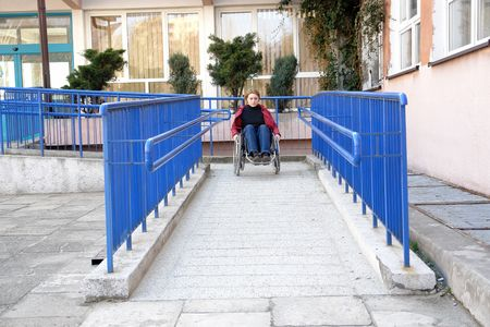 on ramp: Handicapped woman on wheelchair leaving the building using ramp for disabled Stock Photo