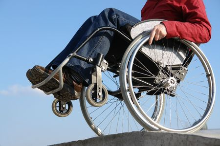 impairment: Closeup of handicapped woman balancing on wheelchair by the concrete kerb over blue sky