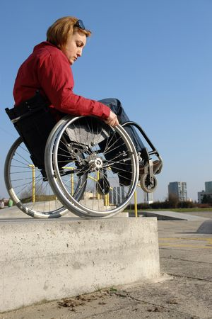 kerb: Handicapped woman on wheelchair going down the high concrete kerb