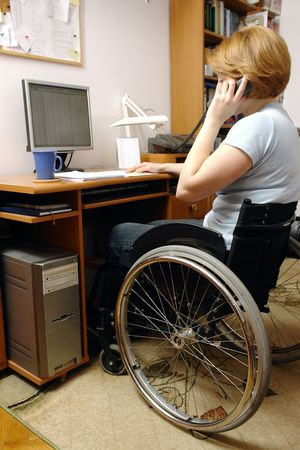 Handicapped woman on wheelchair working at home with computer talking on the phone photo
