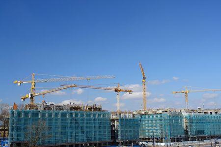 residential settlement: Construction site of residential settlement with group of yellow jib cranes over blue sky