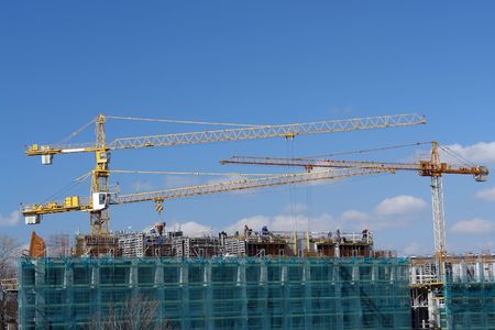 residential settlement: Construction site of residential settlement with group of yellow jib cranes and workers over blue sky