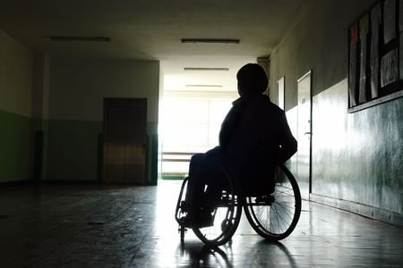 Silhouette of handicapped woman sitting on wheelchair in hospital hallway looking towards the light coming throuth the window