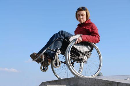 persona en silla de ruedas: Mujer en silla de ruedas por el equilibrio concretas sobre el bordillo azul cielo