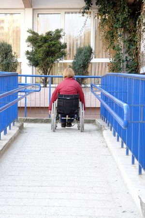 Handicapped woman on wheelchair entering the building using ramp for disabled photo