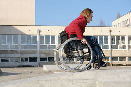 on ramp: Handicapped woman practicing wheelchair riding over obstacle course for disabled